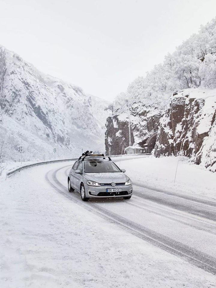 Volkswagen e-Golf Gris con porta esquís circulando por una carretera nevada