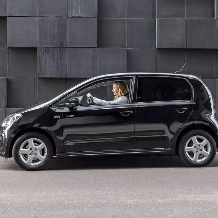 Volkswagen e-Up! negro visto de costado en la calle conducido por una chica