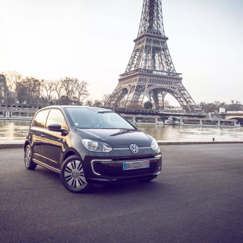 Un Volkswagen e-Up! negro aparcado frente al río Sena y la torre Eiffel