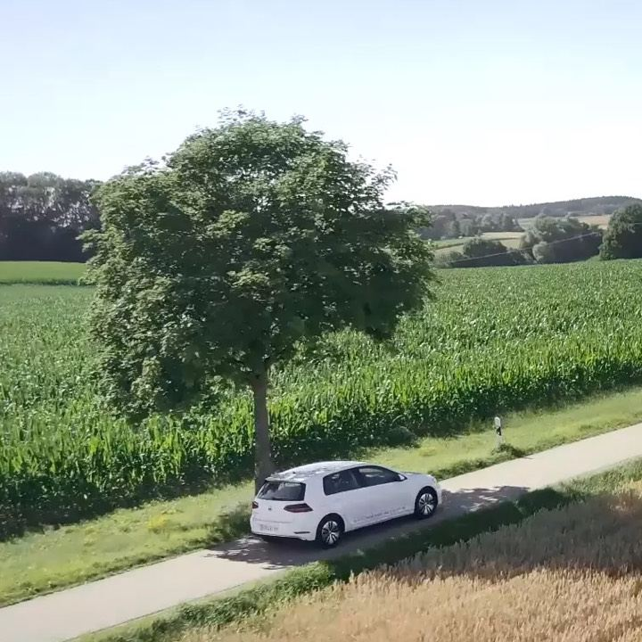 Volkswagen eléctrico circulando por una carretera en el campo bajo la sombra de un árbol