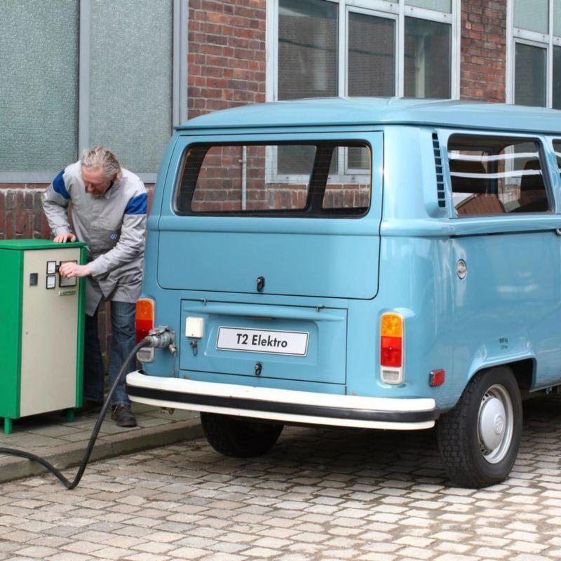 Hombre cargando una furgoneta eléctrica retro azul celeste de Volkswagen en la ciudad