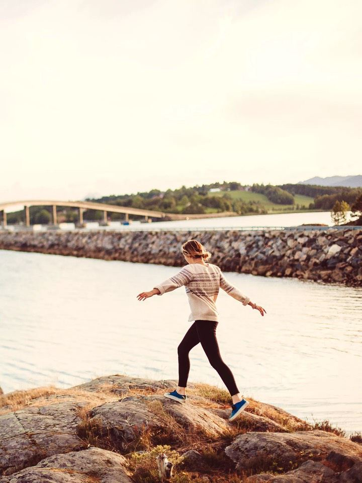 Chica andando con los brazos en alto por las rocas en la orilla del mar al atardecer