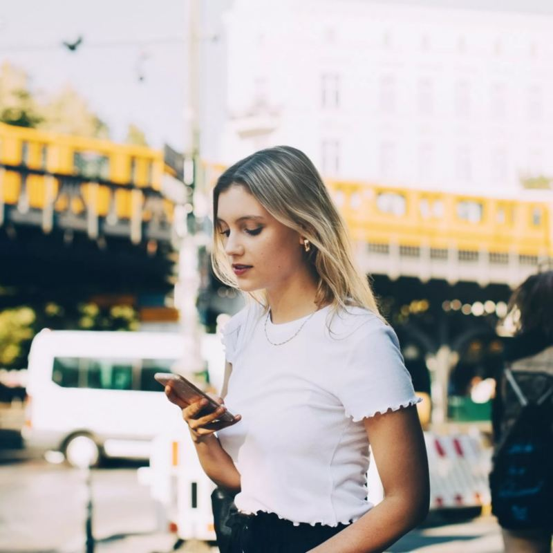 Chica vestida de blanco mirando el móvil en la ciudad