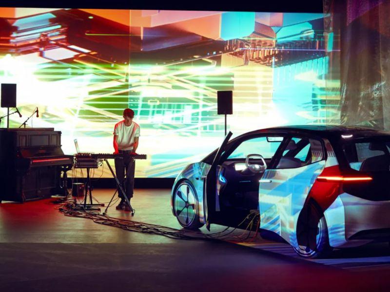 DJ en un escenario con un Volkswagen ID. 3 blanco y luces de colores