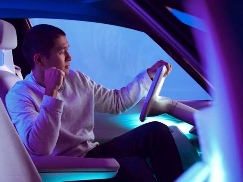Hombre al volante de un Volkswagen eléctrico visto de lado e iluminado por luces azules