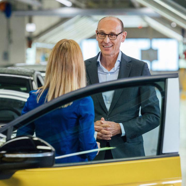 Un hombre y una mujer hablando junto a un Volkswagen ID.4 amarillo con la puerta abierta