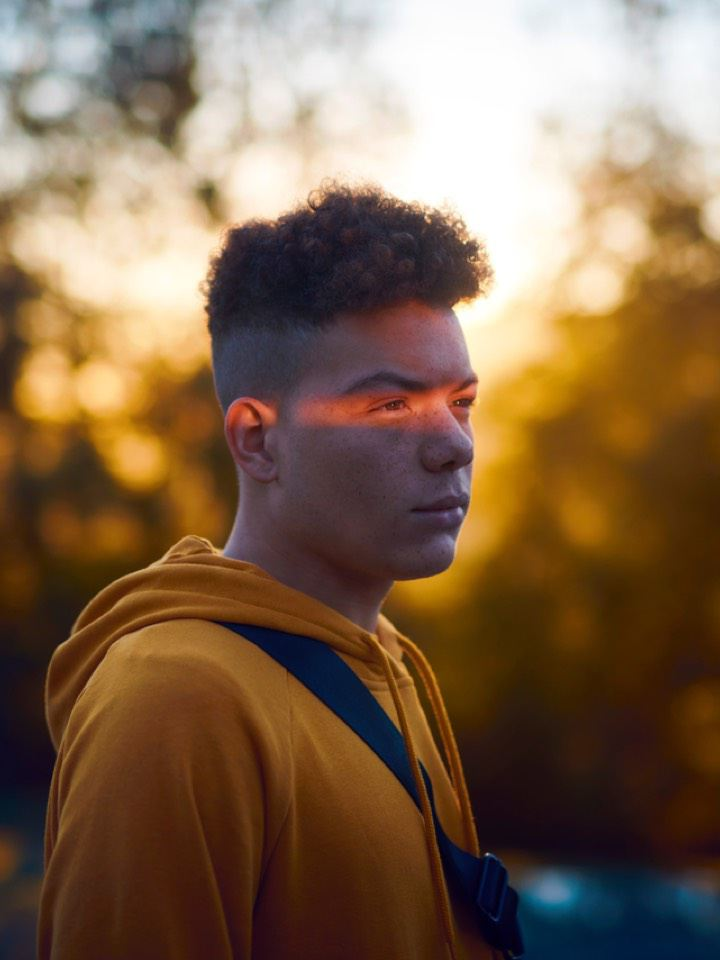 Chico de amarillo en el bosque con una luz en los ojos