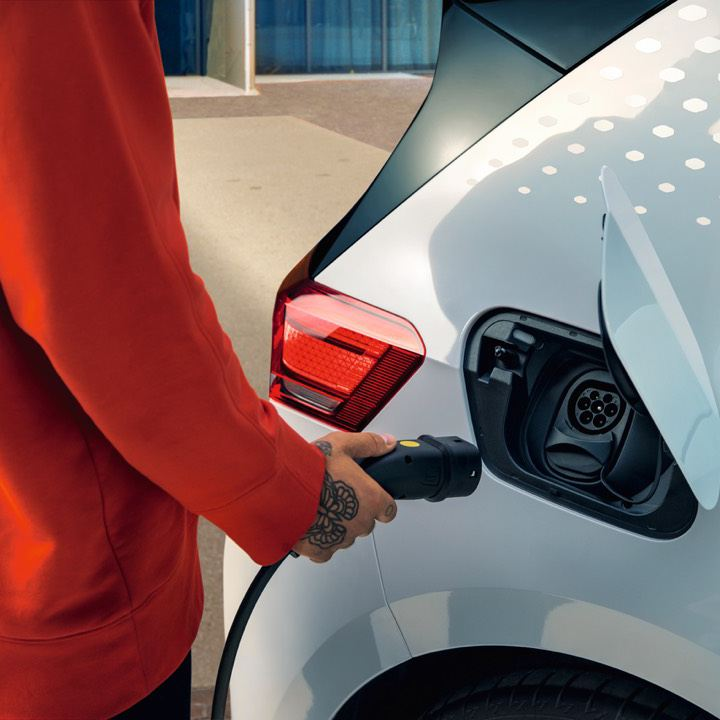 Detalle de una mano conectado un cargador a un Volkswagen ID. 3 blanco