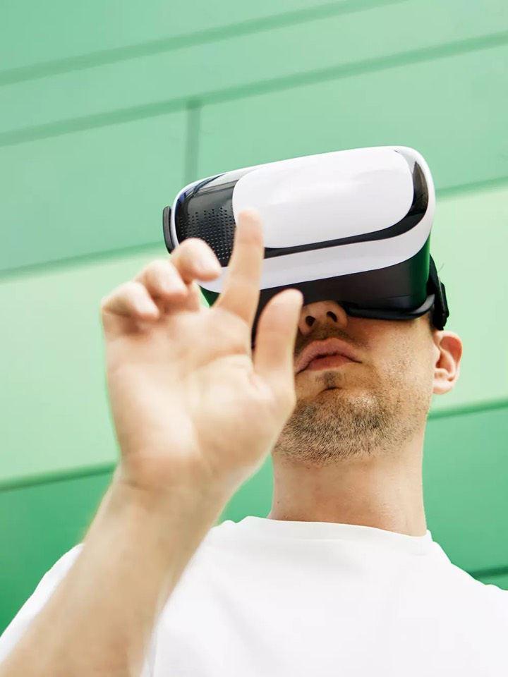 Chico levantando la mano con unas gafas de realidad aumentada frente a una pared verde