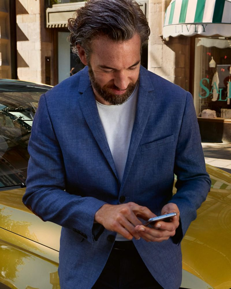 Man using smartphone by a Volkswagen car