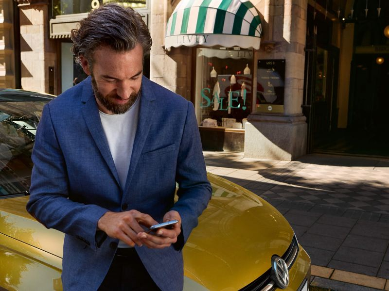 Man in suit leaning on Volkswagen car using smartphone