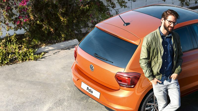 Man casually leaning against an orange Volkswagen Polo car
