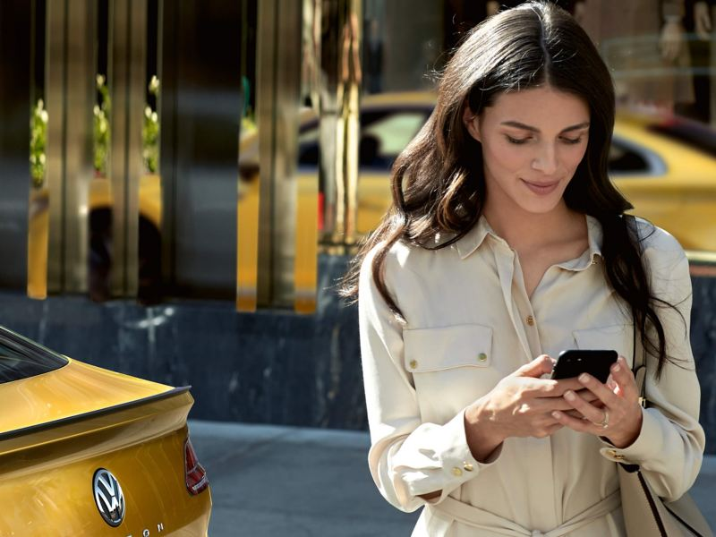 Woman using smartphone by Volkswagen car