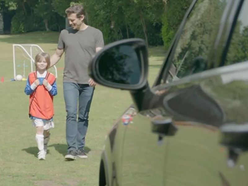 Father and daughter approaching their Volkswagen.