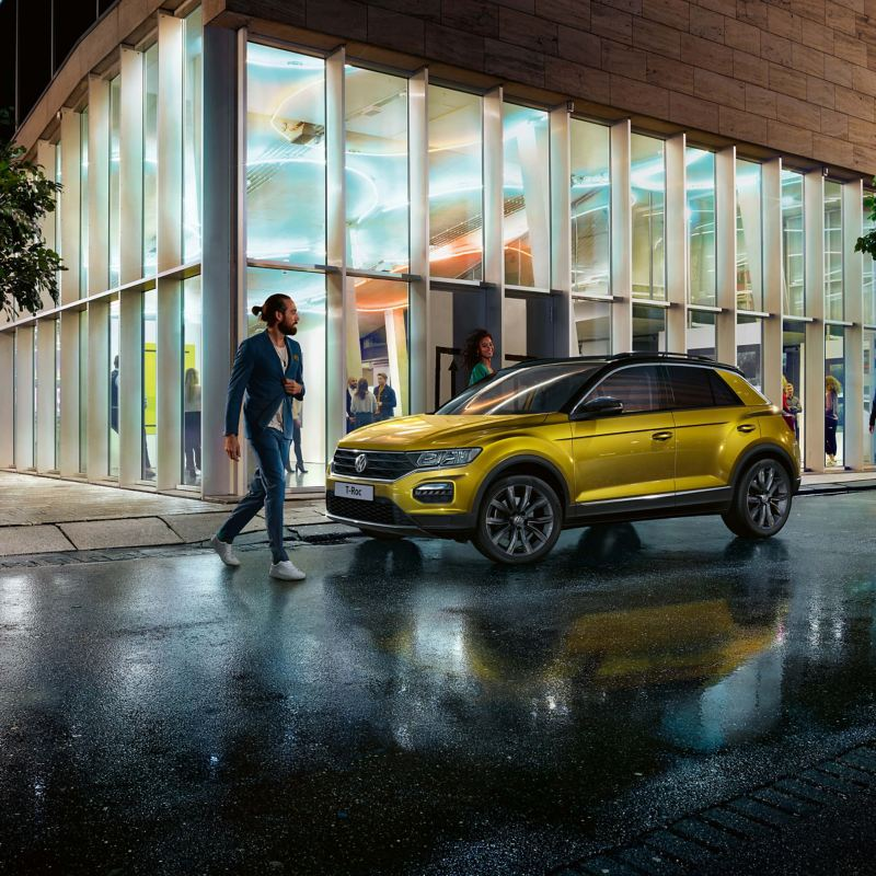 A yellow Volkswagen T-Roc parked in a well lit city street at night.