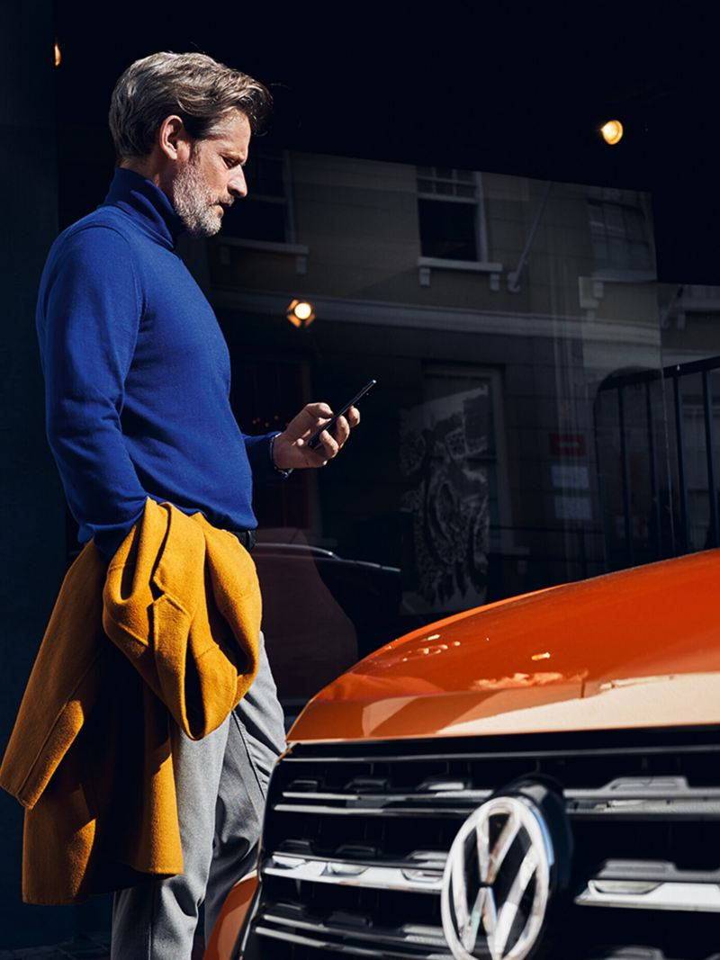 A man looks at his smartphone, his vehicle is in the foreground