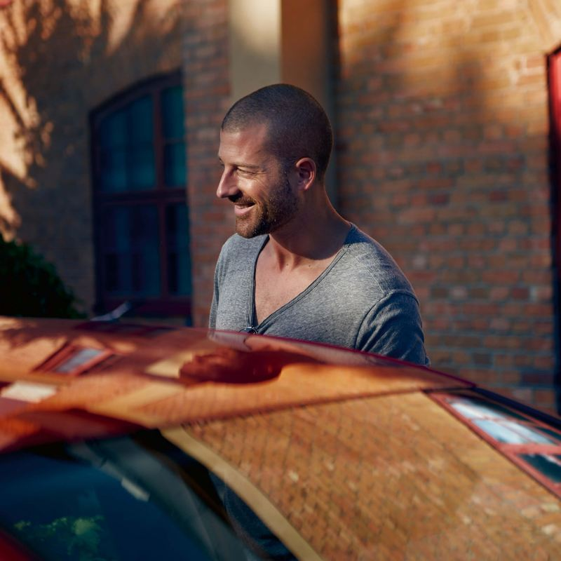 Man smiling by a Volkswagen car