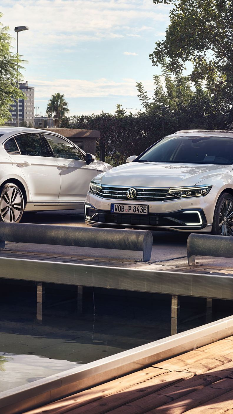 Two Passat GTE models parked over a waterway.