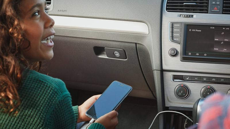 A girl holding a mobile phone inside a car