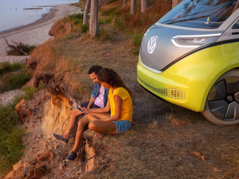 A couple on a cliff face next to a beach and the Volkswagen ID. behind them.