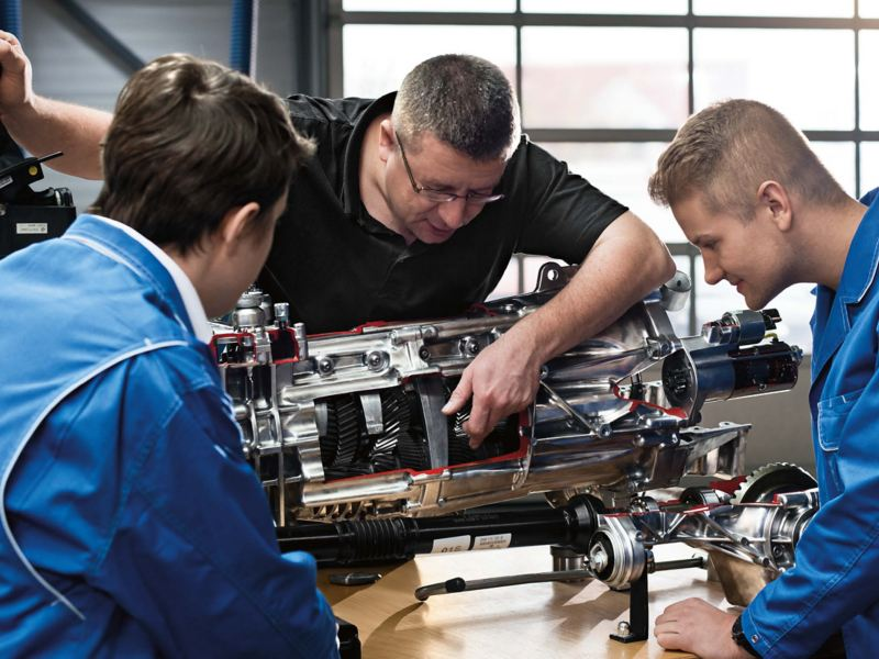 three_mechanics_looking_at_engine