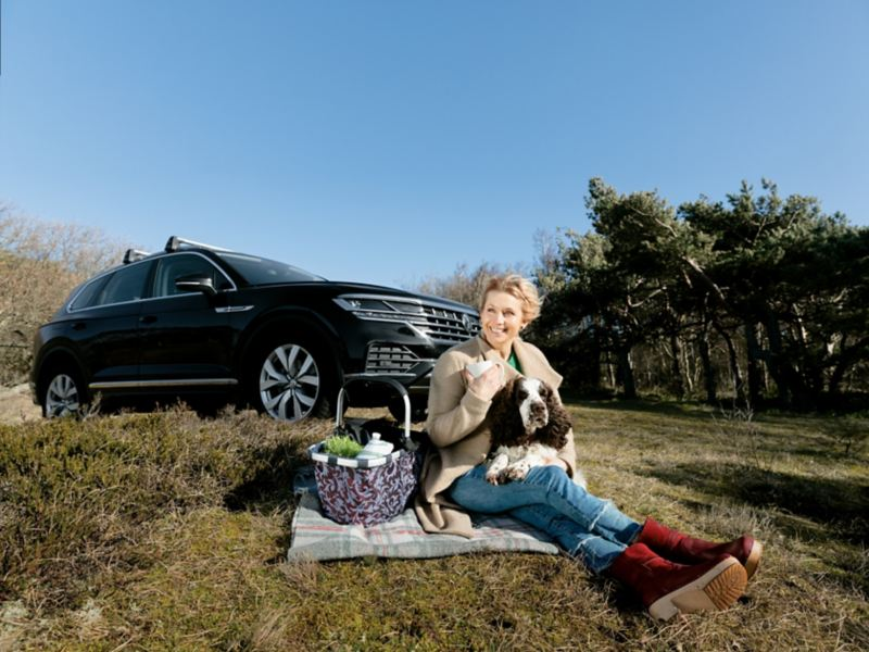 Tina och hund sitter bredvid en Volkswagen Tiguan