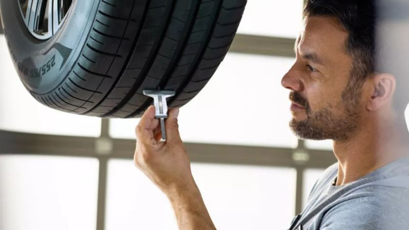 A person is checking a tire with tool