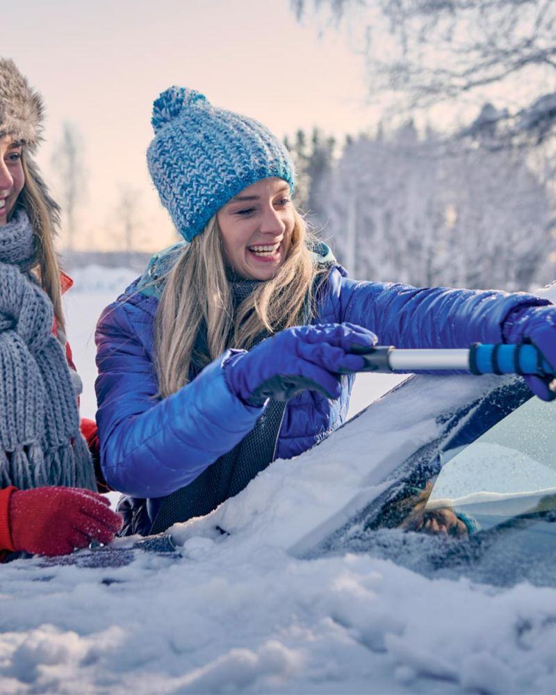 Två tjejer skrapar glatt bort snö från bilen med snöskrapan från Volkswagen