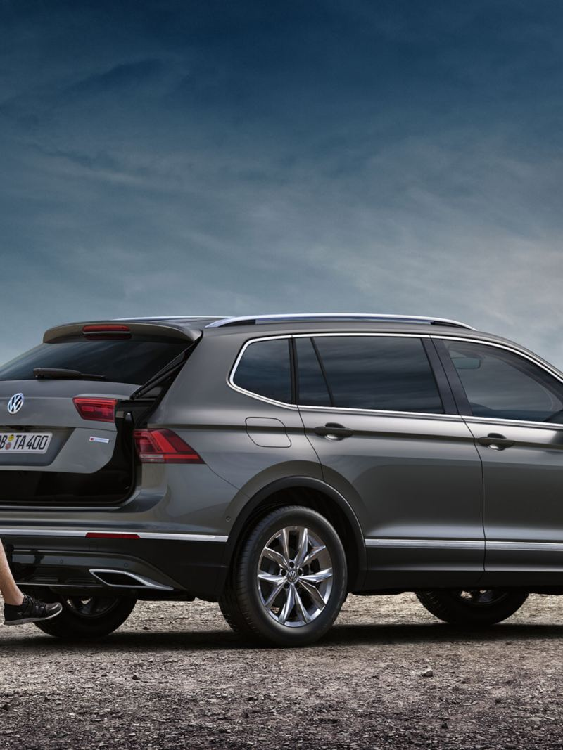 Man opens the boot of the VW tiguan Allspace with his foot under the car