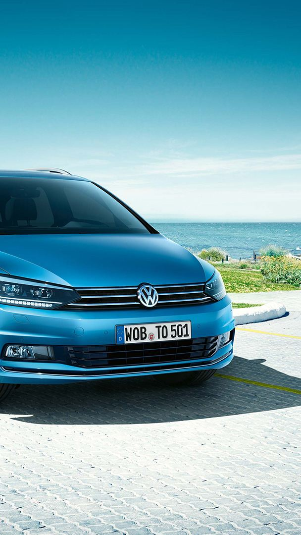 Vista frontal do Volkswagen Touran num estcionamento frente ao mar