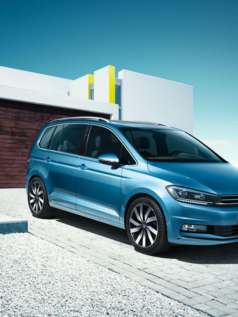 Sininen Volkswagen Touran talon edustalla pysäköitynä ja kuvattuna etuviistosta. Auton takana on perhe kävelemässä