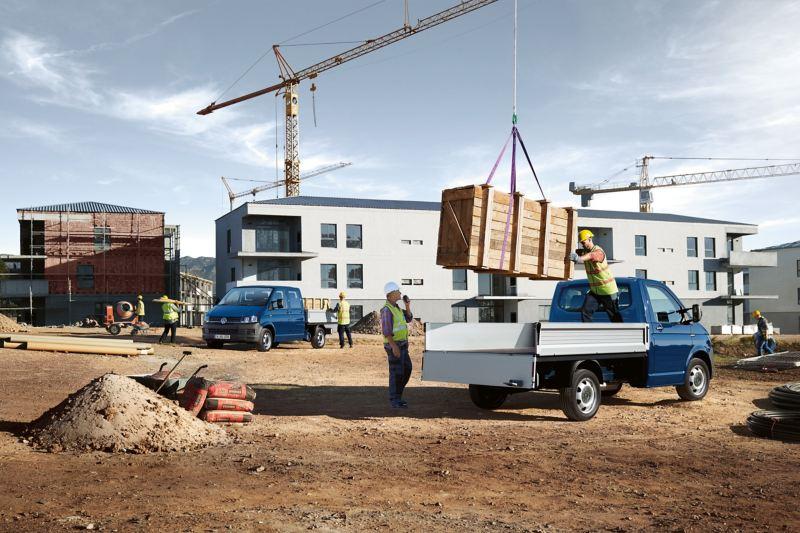 Ein Kran auf einer Baustelle belädt einen Pritschenwagen.