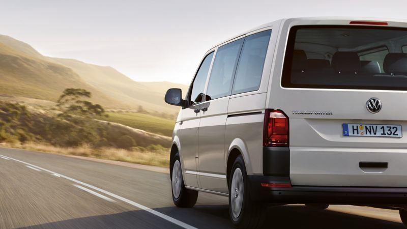 Ein VW Transporter fährt durch eine karge Landschaft.
