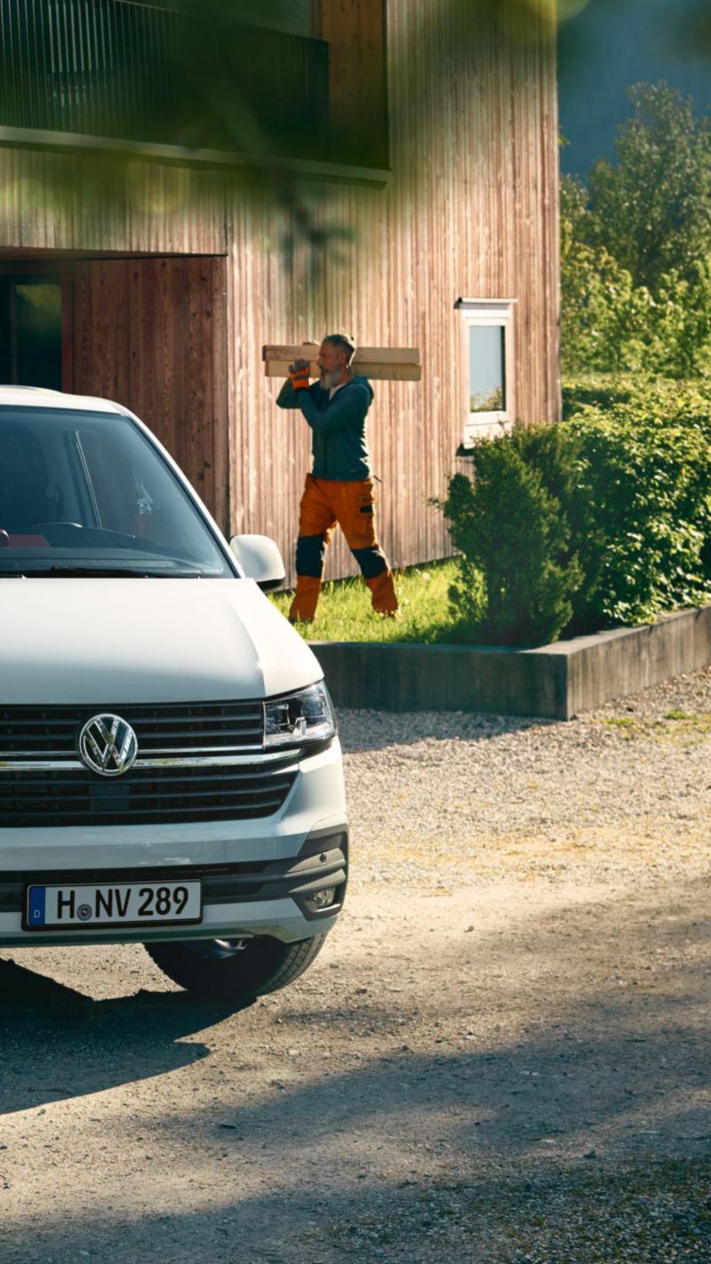 Ένα Volkswagen Transporter 6.1 μπροστά από ξύλινο σπίτι.