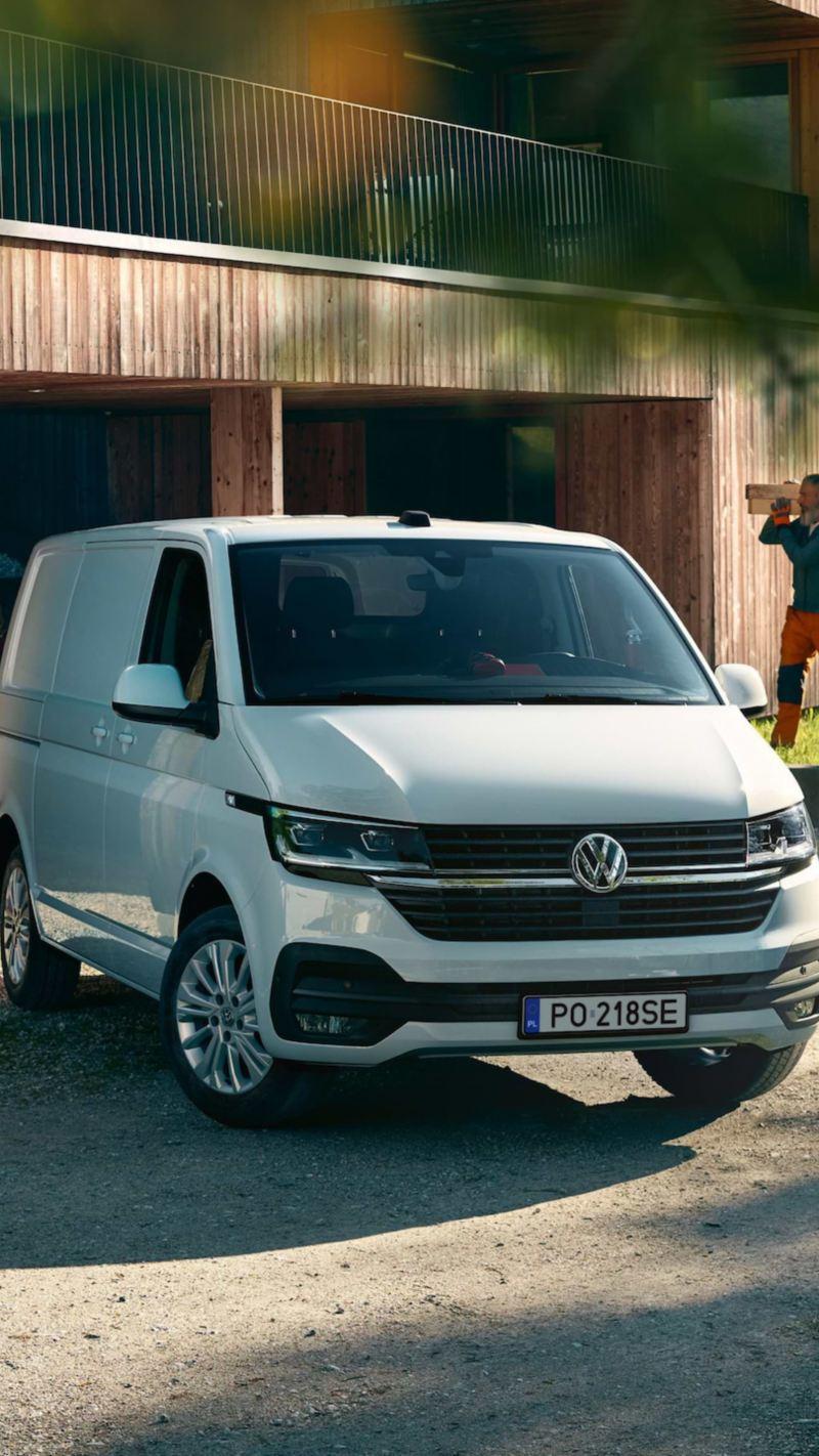Volkswagen Transporter 6.1 przed drewnianym domem.