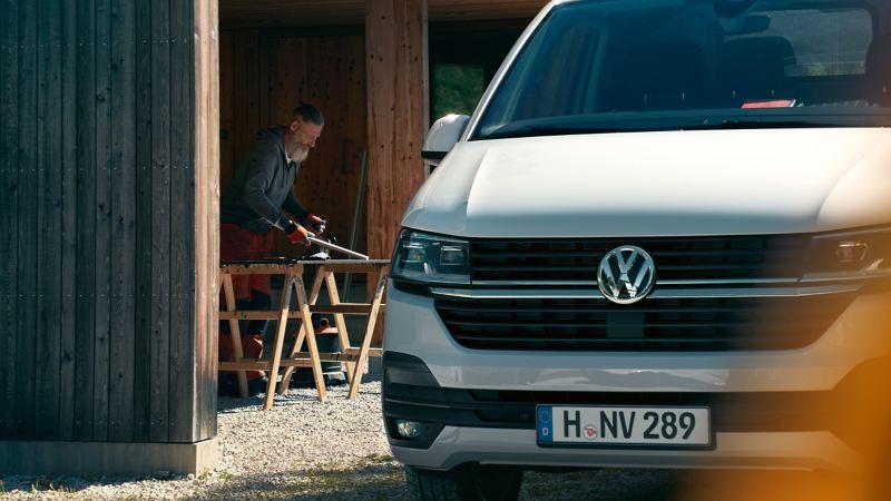 VW Transporter 6.1 med en hantverkare i bakgrunden