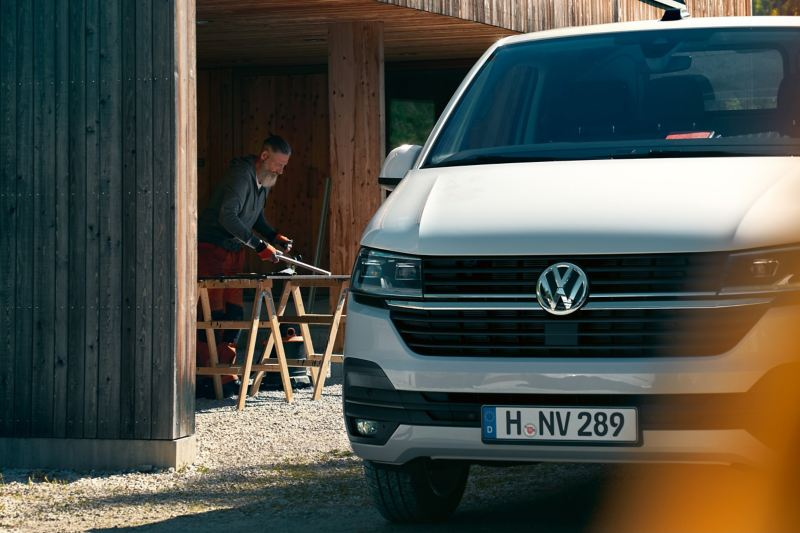 The Transporter 6.1 Delivery Van in front of a wood workshop.