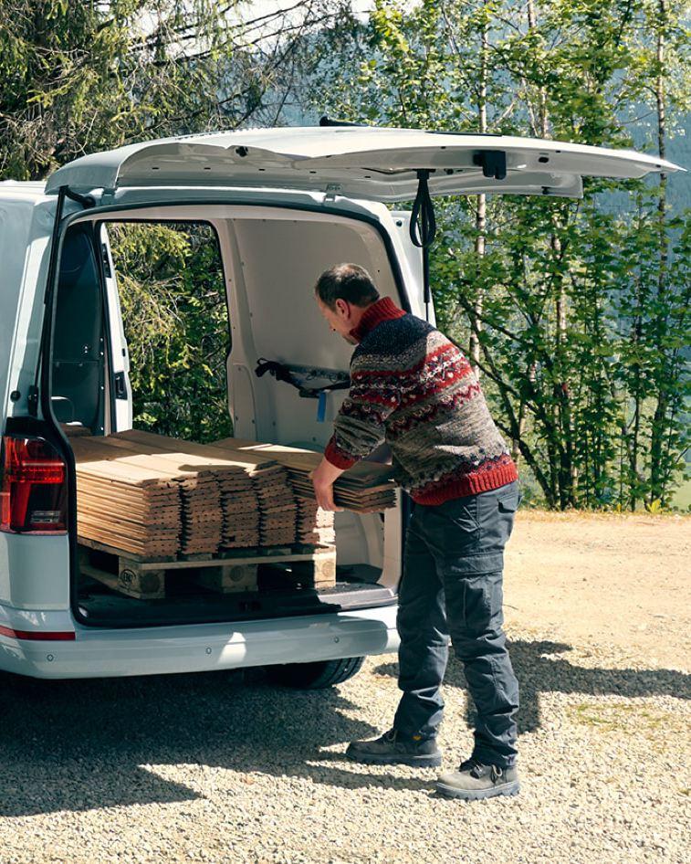 Zwei Männer beladen das Heck eines Transporters mit Holzlatten.