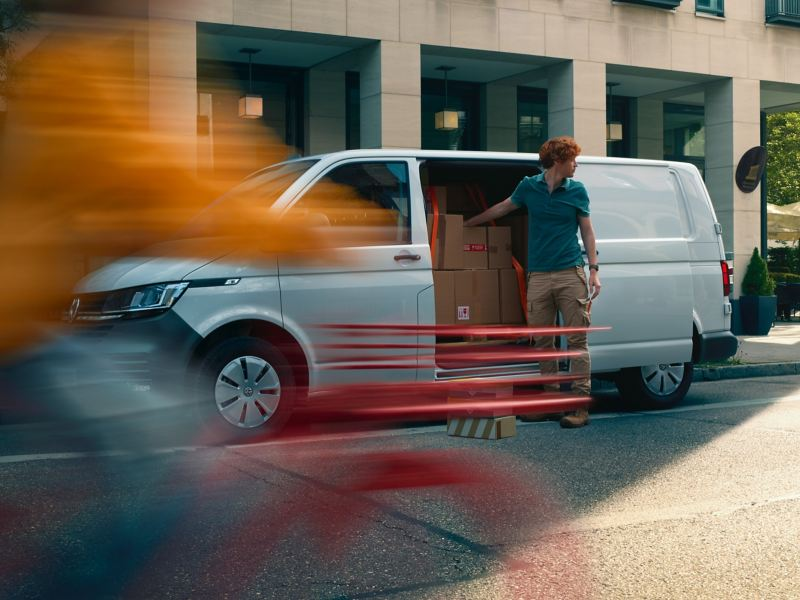 A Volkswagen Transporter 6.1 Delivery Van is standing on the side of a street, a man is unloading packages through the sliding side door.