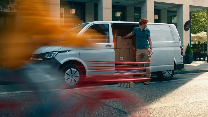Vista laterale di Transporter Volkswagen dal quale un uomo sta scaricando alcuni pacchi.