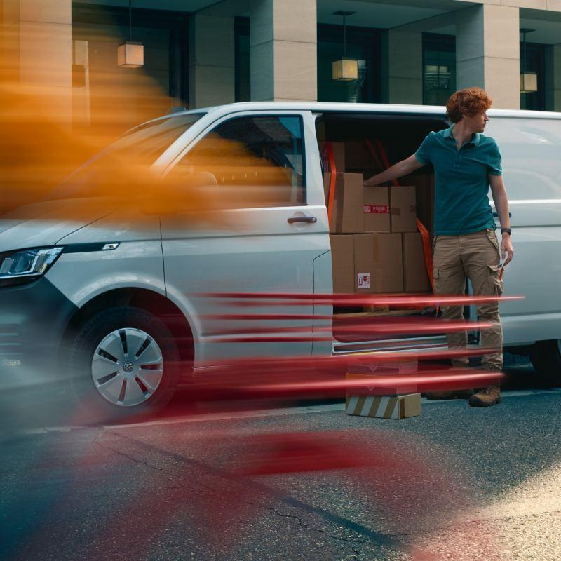Man står utanför sidodörr på en vit VW Transporter Skåpbil