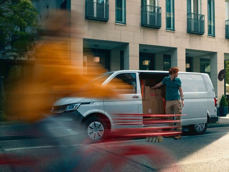 Bildet viser en hvit Volkswagen Transporter varebil som står parkert i bysentrum og en budsjåfør som tar pakker ut av varerommet