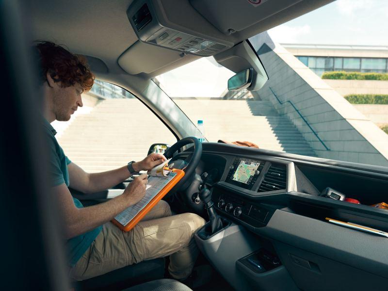 Ein Mann sitzt auf dem Fahrersitz und schreibt auf Formulare auf einem Klemmbrett.