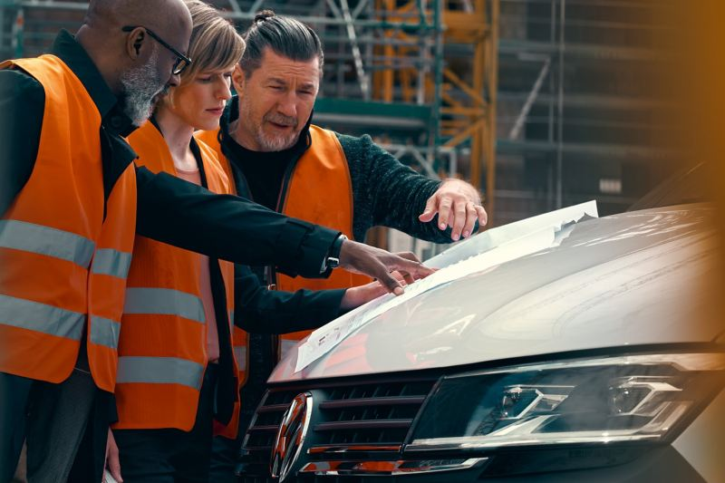 Workers are looking at documents on the engine hood of the Volkswagen Transporter 6.1 Kombi.