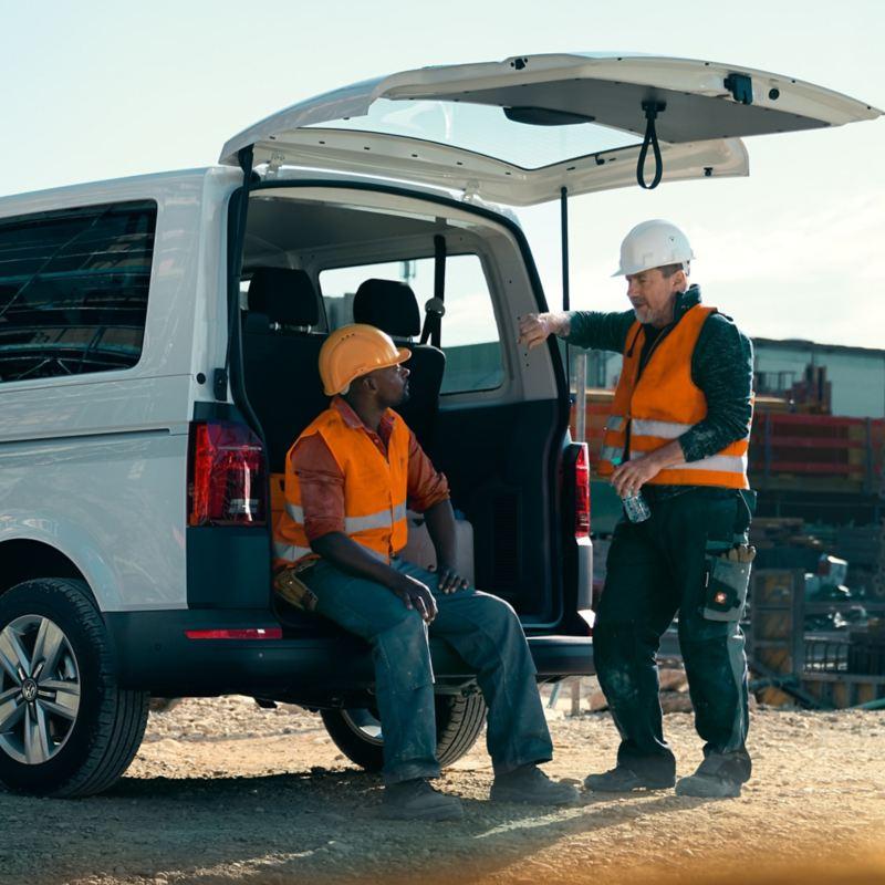 Zwei Bauarbeiter machen Pause bei offenem Kofferraum eines Volkswagen Transporters.
