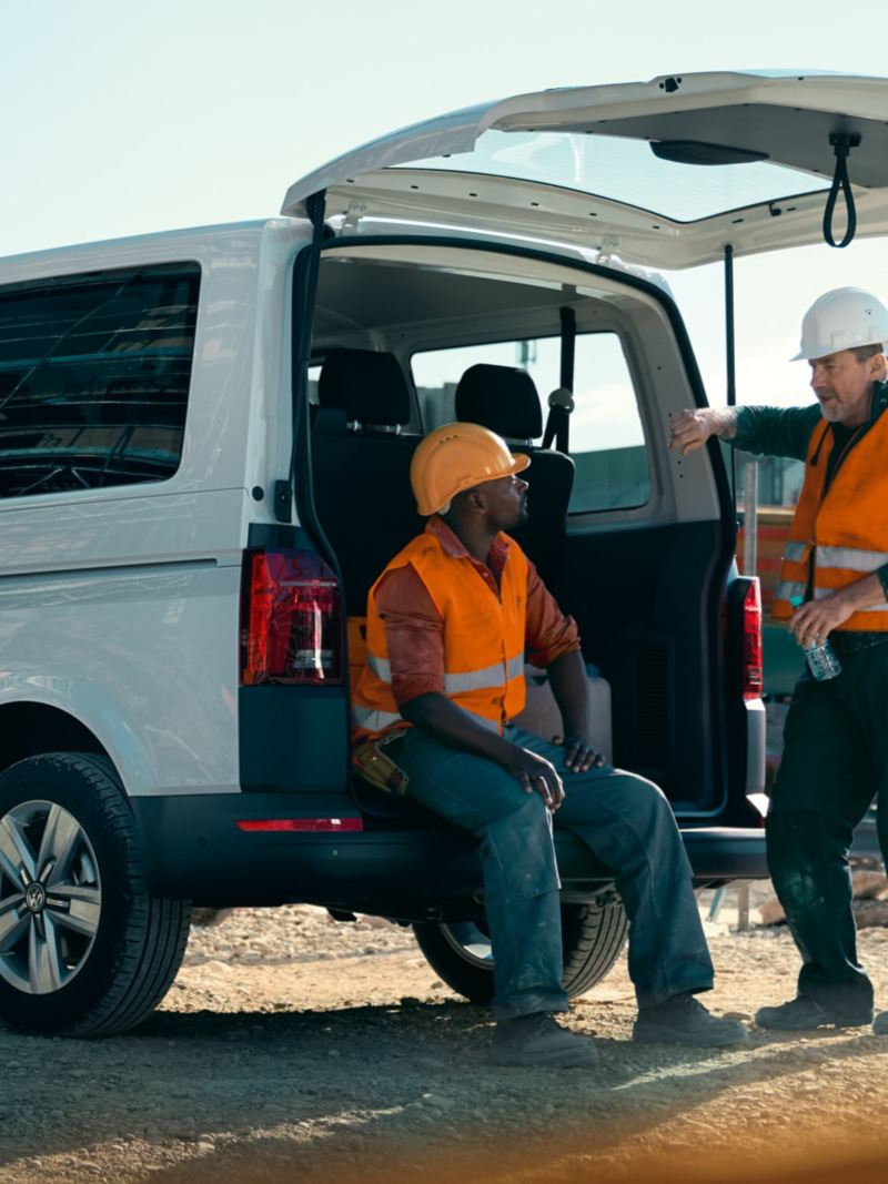 The Volkswagen Transporter 6.1 Kombi is standing on a construction site, two workers are on their break.