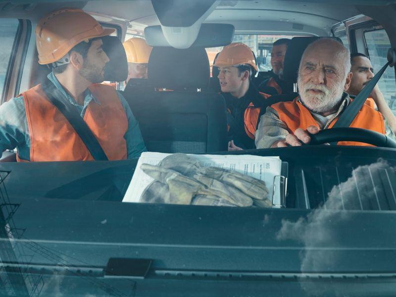 Seven workers are sitting in a Volkswagen Transporter 6.1 Kombi.