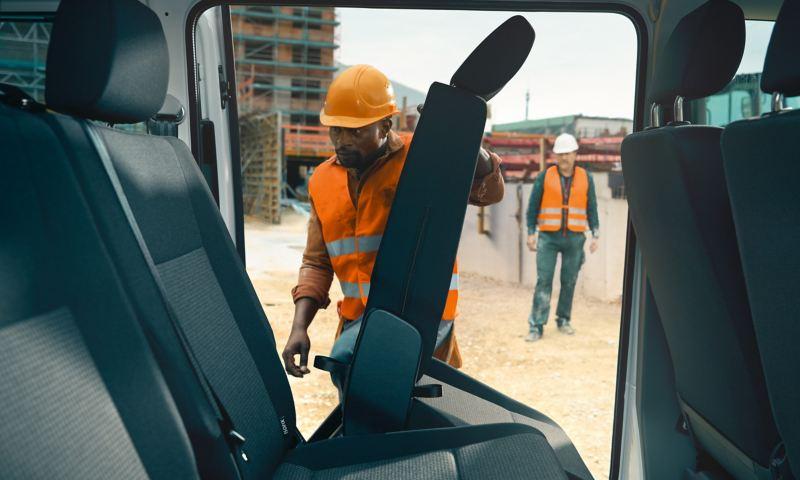 Ein Arbeiter klappt im Volkswagen Transporter 6.1 Kombi einen Sitz zurück.