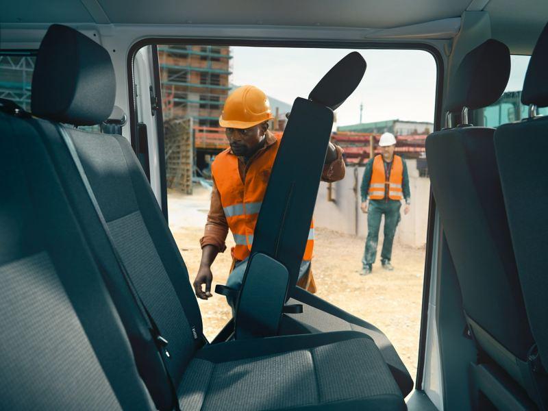 Um homem puxa as costas rebatíveis de um banco traseiro de passageiros da carrinha Transporter 6.1 Kombi.