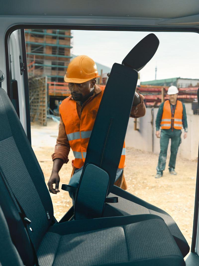 A worker is folding a seat in the Volkswagen Transporter 6.1 Kombi.